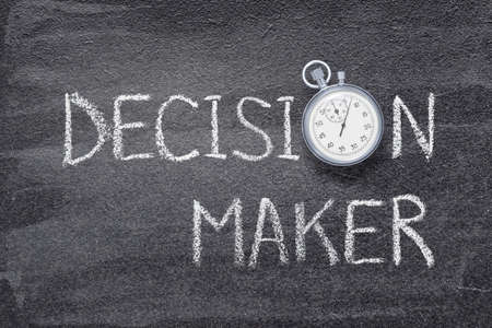 decision maker phrase written on chalkboard with vintage precise stopwatch