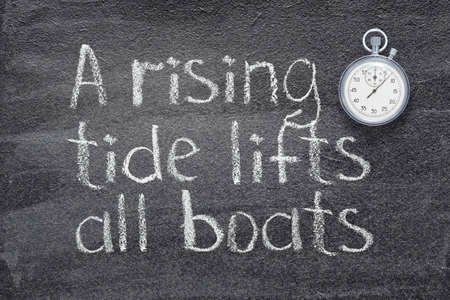 a rising tide lifts all boats proverb written on chalkboard with vintage precise stopwatch