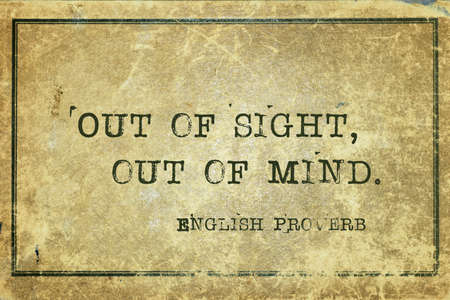 Out of sight, out of mind - ancient English proverb printed on grunge vintage cardboard