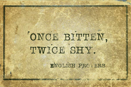Once bitten, twice shy - ancient English proverb printed on grunge vintage cardboard