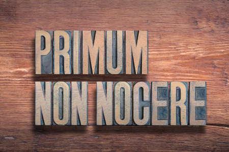 Primum non nocere ancient Latin saying meaning - First, do no harm, combined on vintage varnished wooden surface