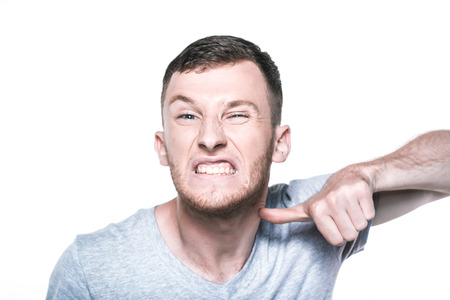 irate: Very angry young man on whited Stock Photo