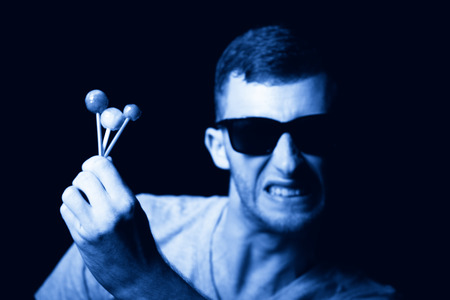 agressive: Agressive young man with lollipops in hand