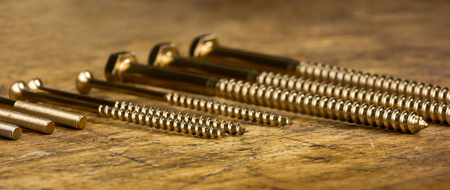Set of golden screws and bolts on wooden background. Symbolic repair tool Stock Photo