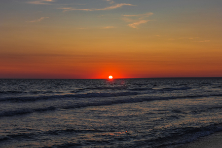 The sun sets over the horizon on the sea Stock Photo