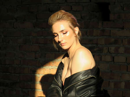 A girl in a black leather jacket and trousers with bare shoulders against a brick wall in a Sunny strip of light