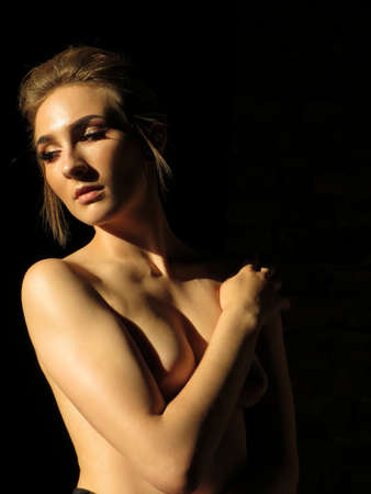 Portrait of a naked girl on a dark background in sunlight