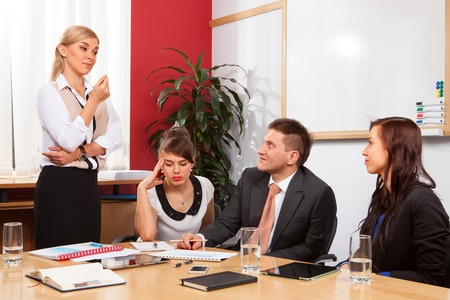 Young businesswoman presenting to partners in meetingroom.