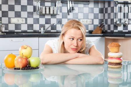 comiendo fruta: Mujer que elige entre frutas y pasteles en la cocina