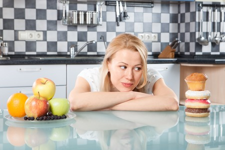 woman eating fruit: Woman choosing between fruits and cakes in the kitchen