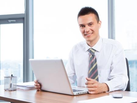 personas sentadas: hombre de negocios joven que trabaja en la oficina con el ordenador port�til Foto de archivo