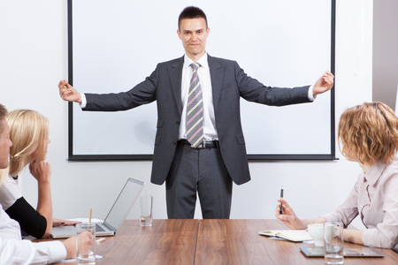 Business team motivated by positive presenter in meeting room