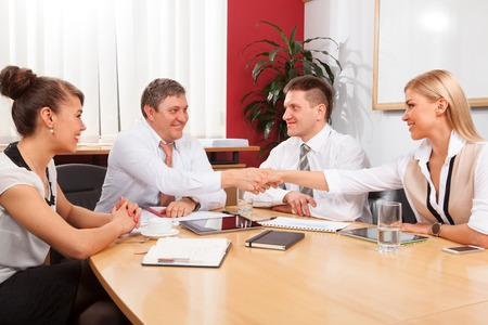 teamworking: Group of businesspeople sitting at meeting table and working together Stock Photo