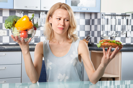Woman choosing between vegetables and sandwich in the kitchen