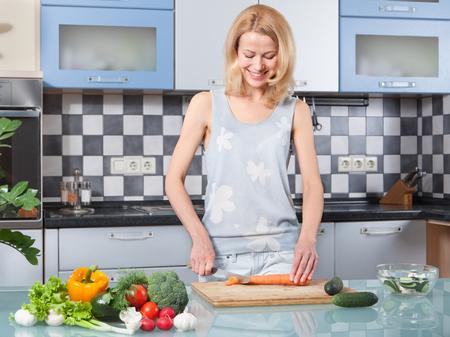case moderne: Giovane donna tagliare le verdure in cucina