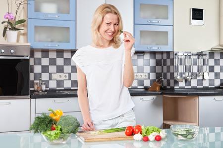 cucina moderna: Giovane donna tagliare le verdure in cucina