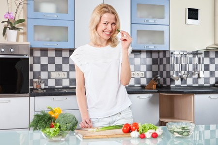 modern lifestyle: Young woman cutting vegetables in the kitchen Stock Photo