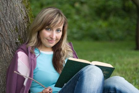 cute girl is sitting under the tree and reading the book