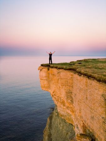 cliff edge: young man standing on the cliff with spreaded hands
