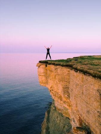 edges: young man jumping on the cliff with spreaded hands Stock Photo