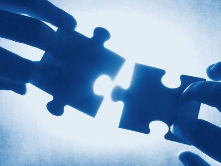 hands trying to fit two puzzle pieces together Stock Photo - 406376