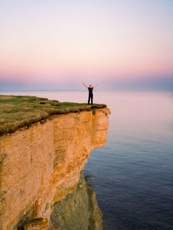 young man standing on a cliff with raised hands