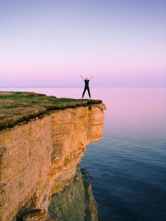 happy man jumping on a cliff Stock Photo