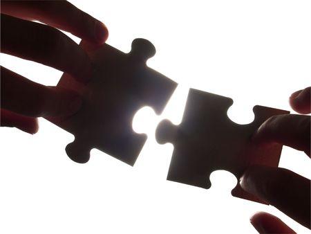 Deux mains essayant d'adapter des morceaux de puzzle, isolé avec chemin de détourage
