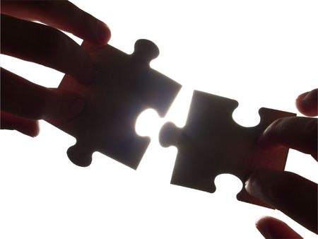 two hands trying to fit puzzle pieces, isolated with clipping path photo