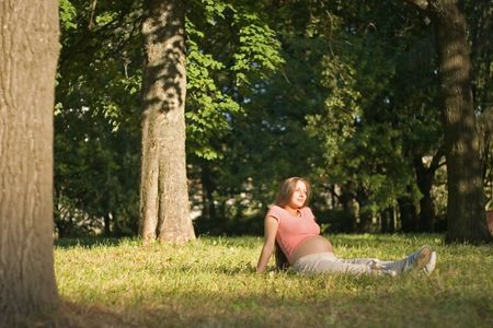 young pregnant woman is sitting in the park among the trees photo