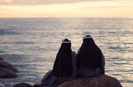 two nuns sitting at the stone on the shore of baltic sea photo