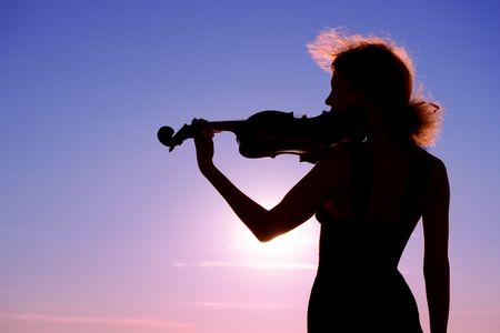 violin player performing solo at sunset