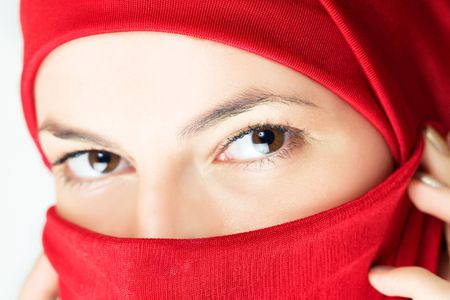 mystery of faith: young woman  in red veil, close-up shot Stock Photo