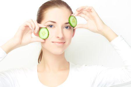 jonge vrouw, met twee plakjes komkommer over haar gezicht, heldere huid concept thema Stockfoto