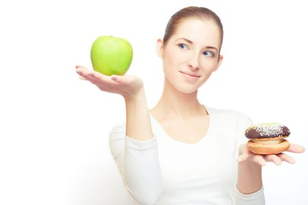 Portrait of young cheerful woman choosing between apple and cake, over white, with some shadows left photo