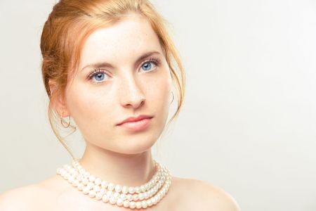 portrait of young beautiful girl with pearl necklace photo