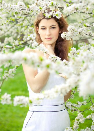 portrait of young brunette in the spring garden photo