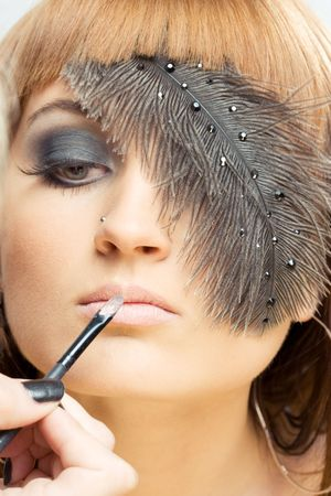 hair feathers: close up of make-up artist applying lipstick Stock Photo