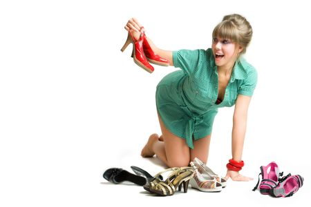 young blonde choosing her shoes, isolated over white photo