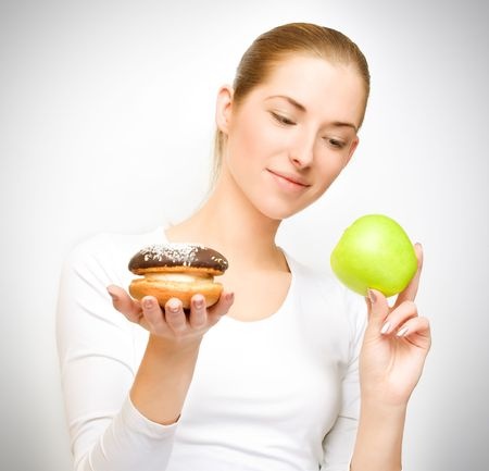 choosing between apple and cake - healthy eating concept photo