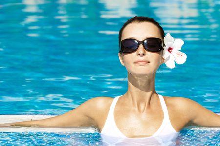 수영장에서 태양을 즐기는 화려한 갈색 머리