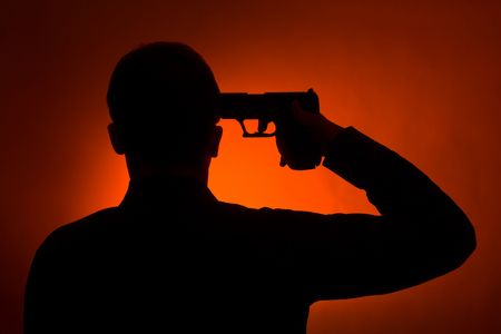 silhouette of the man pointing gun to his head, ready to commit suicide photo