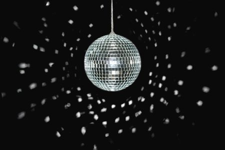 mirrorball: spinning discoball, over black background, light reflections