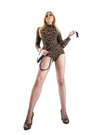 domination: young blonde with whip posing over white, wide angle shot Stock Photo