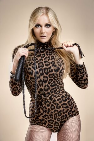 domination: young blonde with whip posing, studio shot Stock Photo