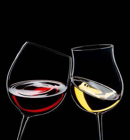 Copas de vinos rojos y blancos, aislados sobre negro, espacio para la copia