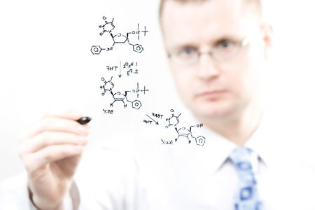 chemist's: young chemist writing organic chemistry reaction equation, selective focus Stock Photo