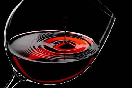 wine background: glass of red wine, drops in motion, studio shot