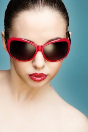 빨간색 선글라스를 착용하는 젊은 아름 다운 여자의 스튜디오 초상화를 닫습니다