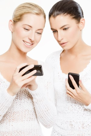 two young caucasian women with smartphones, isolated over white photo